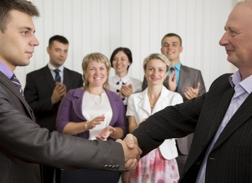 Mature businessman congratulates younger employee standing in front of the happy team